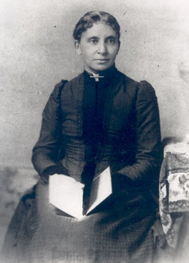 Photograph of Charlotte Forten Grimké holding a book.