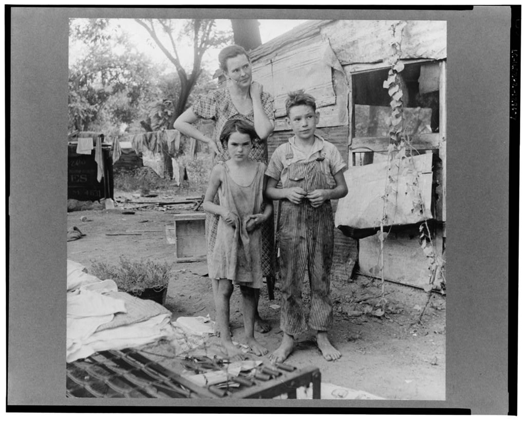A mother and her two children wearing filthy clothing stand in front of their make-shift home. Clothes hang on the line to dry in he background.