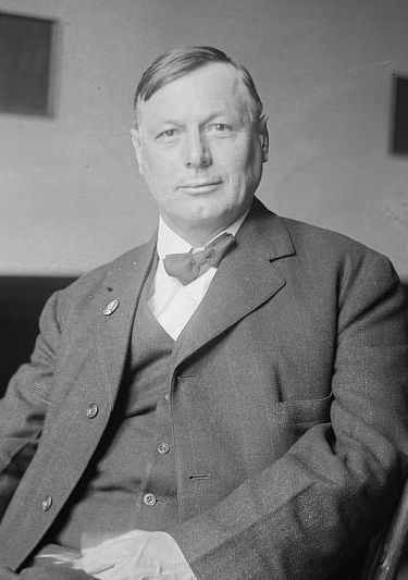Oscar Ameringer, seated, wearing suit and bow tie, slight smile on his clean-shaven face.