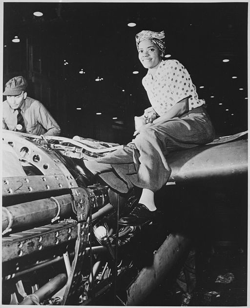 A female, African American worker wearing a head scarf sits on top of the aircraft she is building