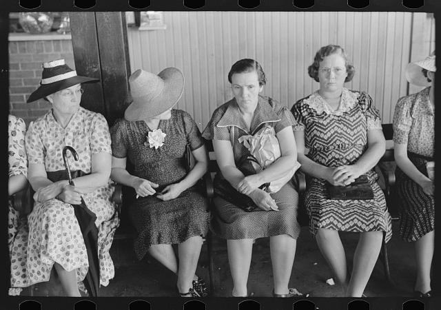Six women in dresses sit on a bench waiting.